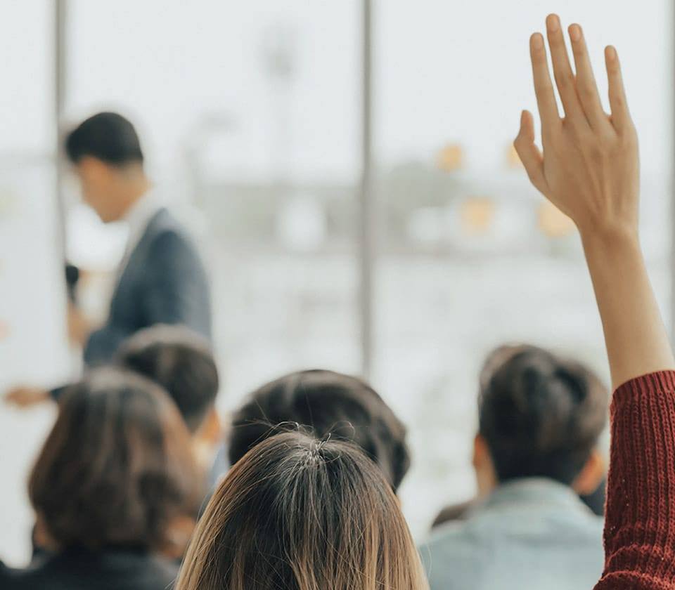 woman with a raised hand in a class