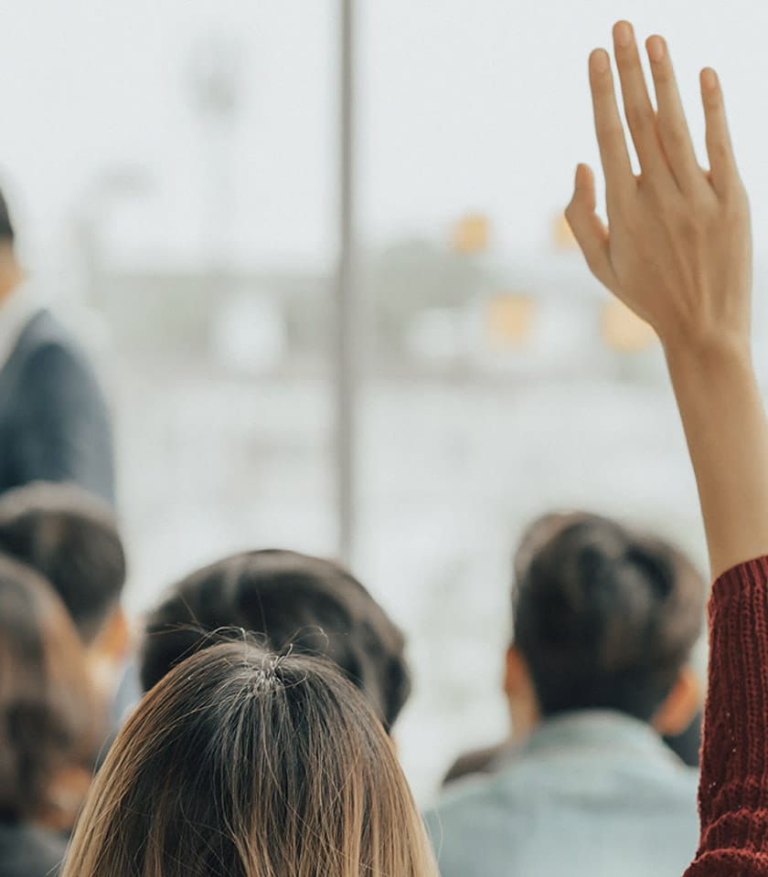 woman with raised hand in a class